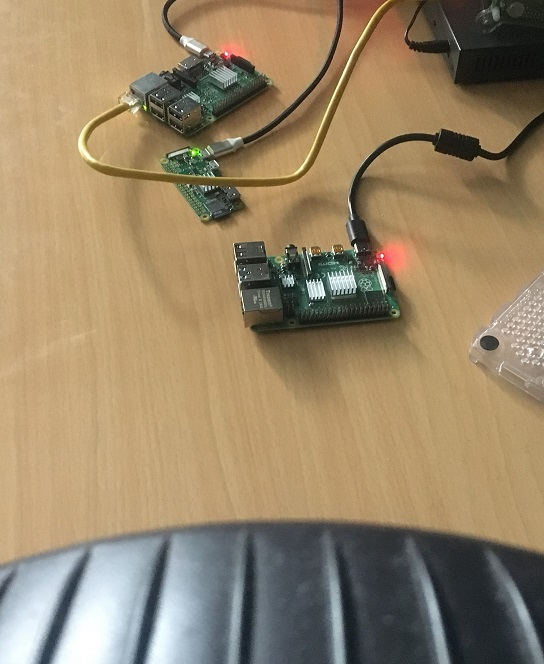 Picture showing the three Raspberry Pis out of their cases under the wind provided by a desk fan.
